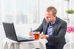 Бизнесмен в офисе сидя на таблице с компьтер-книжкой пишет с концентрацией Стоковое Изображение RF