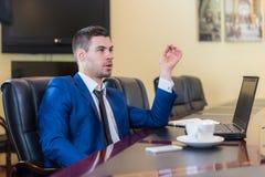 Бизнесмен в офисе с компьтер-книжкой Стоковое Изображение