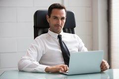 Бизнесмен в офисе с портативным компьютером Стоковое фото RF