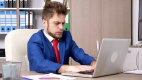 Бизнесмен в официально носке печатая на компьтер-книжке в офисе акции видеоматериалы