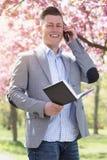Бизнесмен в парке с книгой и телефоном Стоковая Фотография RF