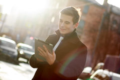Бизнесмен в пальто используя таблетку Стоковое Изображение