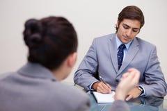 Бизнесмен в переговорах принимая примечания Стоковые Изображения
