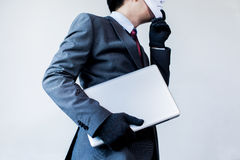 Бизнесмен в перчатках белой маски нося и компьютере красть и цифровая информация - очковтирательство, хакер, похищение, злодеяние стоковые фото