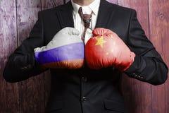 Бизнесмен в перчатках бокса с флагом русского и Китая Россия против концепции Китая стоковые изображения