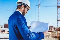 Бизнесмен в планах здания защитного шлема и костюма рассматривая Стоковое фото RF