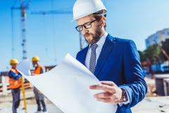 Бизнесмен в планах здания защитного шлема и костюма рассматривая Стоковые Фотографии RF