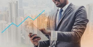 Бизнесмен в положении планшета удерживания костюма над запачканной предпосылкой города и успешным передним планом диаграммы стоковое фото