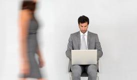 Бизнесмен в прихожей работая на компьтер-книжке, женщина проходя мимо Стоковые Изображения RF