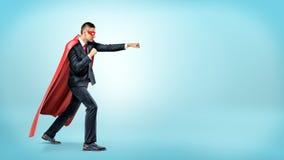 Бизнесмен в пропуская красной накидке супергероя и пунши маски бросая на незримом враге на голубой предпосылке Стоковая Фотография