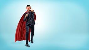 Бизнесмен в пропуская красной накидке супергероя и пунши маски бросая на незримом враге на голубой предпосылке Стоковая Фотография RF