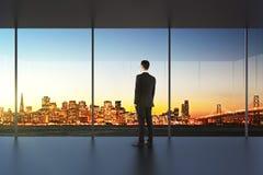 Бизнесмен в пустом офисе смотря красивый горизонт стоковая фотография