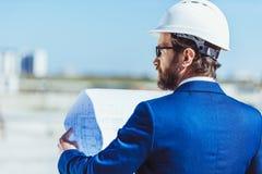 Бизнесмен в рассматривать защитного шлема и костюма Стоковое Изображение