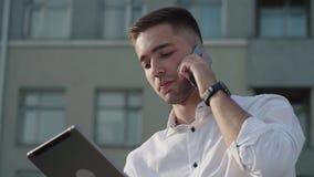 Бизнесмен в рубашке используя планшет пока говорящ телефоном сток-видео