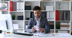 Бизнесмен в серой куртке сидя на таблице в белом листе бумаги офиса и подписания, стучать и бросать сток-видео