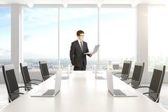 Бизнесмен в современном конференц-зале с мебелью, компьтер-книжками Стоковое Изображение
