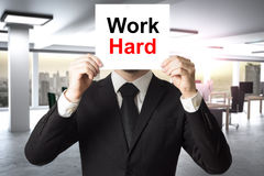 Бизнесмен в стороне большого офиса пряча за работой знака крепко Стоковое Изображение RF