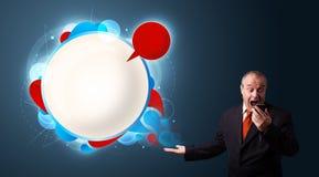 Бизнесмен в сюите держа телефон и представляя абстрактный современный пузырь речи Стоковая Фотография