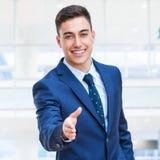 Бизнесмен в сюите достигая вне руку Стоковое фото RF