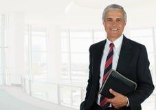 Бизнесмен в установке офиса светлого тонового изображения держа небольшую тетрадь стоковое фото rf