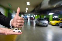 Бизнесмен в черном костюме держа малую модель автомобиля и показывая одобренный знак Стоковые Фотографии RF