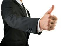 Бизнесмен в черном костюме показывая большие пальцы руки поднимает знак Стоковая Фотография RF