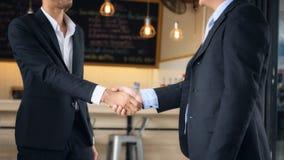 Бизнесмен в черном handshaking костюма Стоковое Изображение