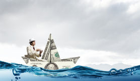 Бизнесмен в шлюпке сделанной банкноты доллара Стоковое Фото
