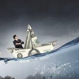 Бизнесмен в шлюпке сделанной банкноты доллара Стоковая Фотография