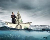 Бизнесмен в шлюпке сделанной банкноты доллара Стоковое Изображение