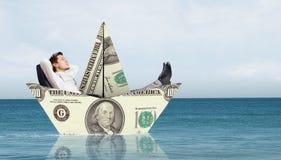 Бизнесмен в шлюпке сделанной банкноты доллара Стоковые Изображения RF