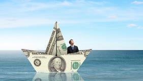 Бизнесмен в шлюпке сделанной банкноты доллара Стоковые Фотографии RF