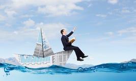 Бизнесмен в шлюпке сделанной из бумаги Стоковое Фото