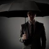 Бизнесмен в costume держа черный зонтик стоковое фото