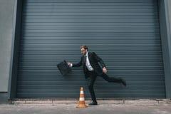 Бизнесмен в eyeglasses держа портфель и ход около конуса движения Стоковая Фотография
