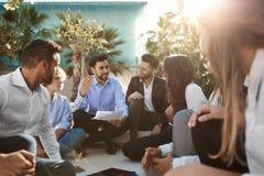 Бизнесмен говоря к сотрудникам сидя снаружи Стоковые Изображения