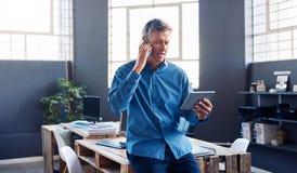 Бизнесмен говоря на его мобильном телефоне и используя цифровую таблетку Стоковое Фото