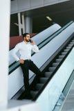 Бизнесмен говоря на мобильном телефоне в офисе на лестницах Стоковые Фотографии RF