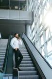 Бизнесмен говоря на мобильном телефоне в офисе на лестницах Стоковые Фото