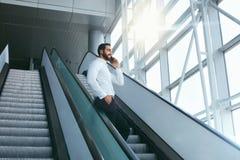 Бизнесмен говоря на мобильном телефоне в офисе на лестницах Стоковые Изображения RF
