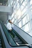 Бизнесмен говоря на мобильном телефоне в офисе на лестницах Стоковая Фотография RF