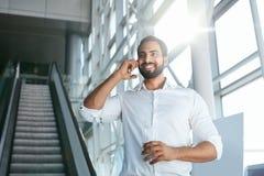 Бизнесмен говоря на мобильном телефоне в офисе на лестницах Стоковое Изображение