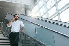 Бизнесмен говоря на мобильном телефоне в офисе на лестницах Стоковое Изображение RF