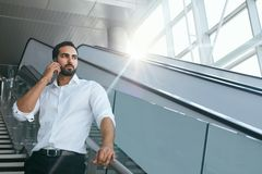 Бизнесмен говоря на мобильном телефоне в офисе на лестницах Стоковое Фото