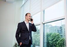 Бизнесмен говоря на мобильном телефоне, бизнесмен говоря на t Стоковые Изображения
