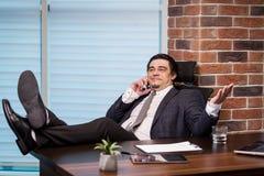 Бизнесмен говоря на мобильном телефоне, бизнесмен говоря на t Стоковая Фотография