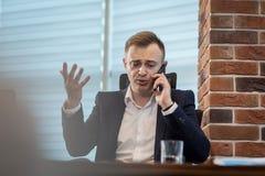 Бизнесмен говоря на мобильном телефоне, бизнесмен говоря на t Стоковое Фото