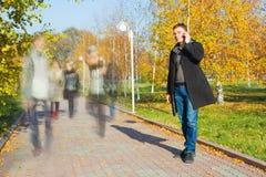 Бизнесмен говоря на мобильном телефоне в парке Стоковое Изображение