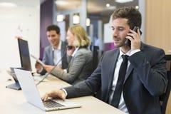 Бизнесмен говоря на мобильном телефоне в современном офисе Стоковые Фото