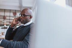 Бизнесмен говоря на мобильном телефоне пока на работе Стоковая Фотография RF